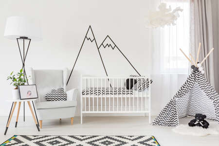 Light functional baby room with cot, play tent and armchair
