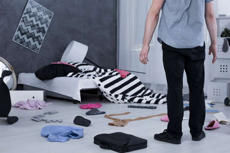 Surprised man standing in messy room with floor full of clothes Standard-Bild