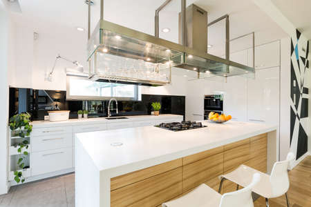 lightsome: Sophisticated loft kitchen with a large kitchen worktop and modern steel hood Stock Photo