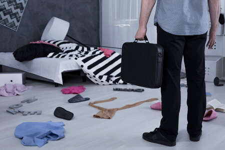 mess: Man standing in a messy room with a suitcase in his hand