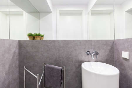 granite wall: Simple small bathroom with gray granite walls, white modern sink and wall mirrors