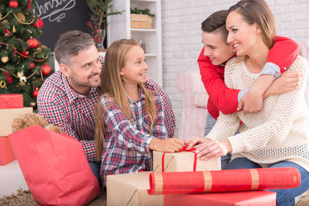 family  room: Happy family packing Christmas presents in living room Stock Photo
