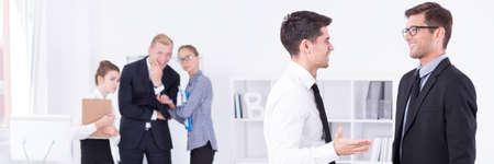 acoso laboral: Dos chicos de traje y corbata hablando en el trabajo