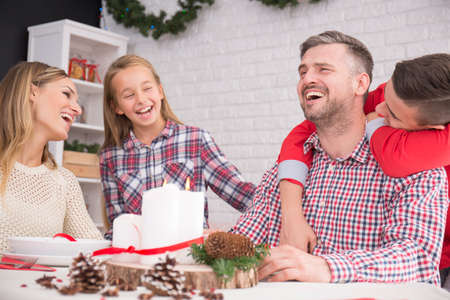 family  room: Family sitting in Christmas decorated dining room and laughing