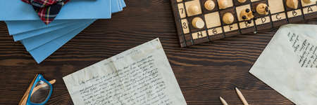 sobres de carta: Old letter, envelopes, glasses and chess board on wooden table