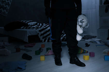rubbery: Burglar standing in dark childrens bedroom and holding a teddy bear