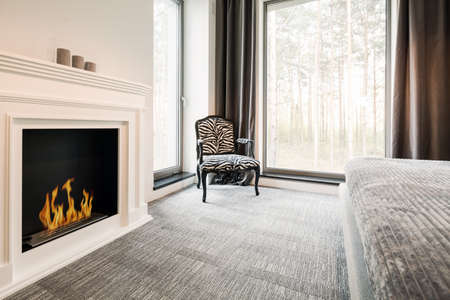 lightsome: Grey master bedroom with elegant fireplace, chair, bed and panoramic window Stock Photo