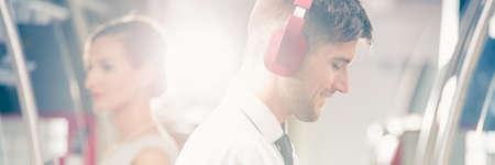 auriculares: Relajado y sonriente hombre con auriculares en el tren