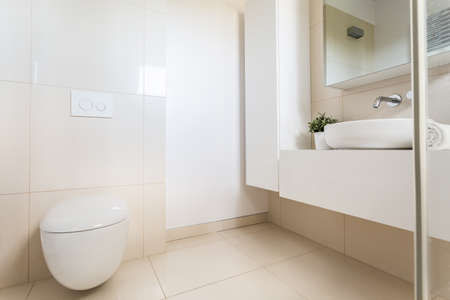 toilet sink: Minimalist bathroom with bright marble tiles, modern toilet, sink and mirror