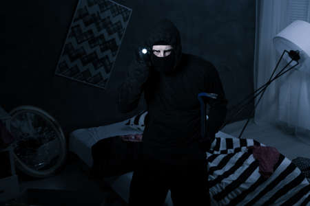rubbery: Robber standing in dark room and holding flashlight and crowbar