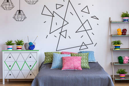 bedroom area: Bedroom area with colourful bed, commode and white wall with triangle theme on