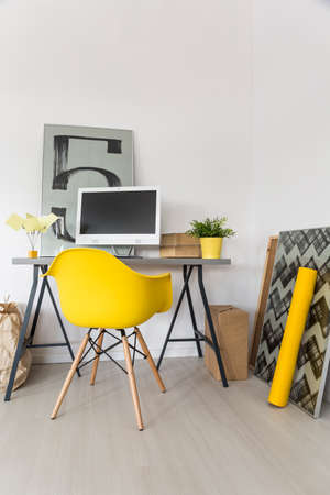 yellow walls: Modern minimalist workplace with light walls and yellow chair