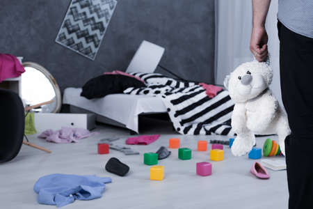 messy room: Man standing in messy childrens room and holding a teddy bear