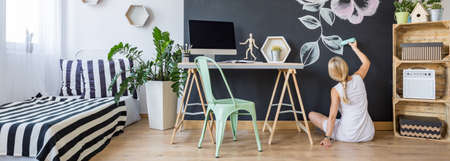Modern creative studio interior and a woman painting on a chalkboard wall Stock Photo - 67277842