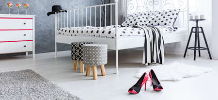 Red high-heels on the floor of female bedroom