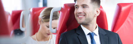 smiled: Smiled and relaxed businessman on modern train seat Stock Photo