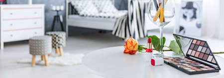 Cosmetics and rose lie on table  in bedroom