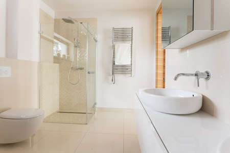 case moderne: Modern spacious bathroom with bright tiles with glass shower, toilet and sink