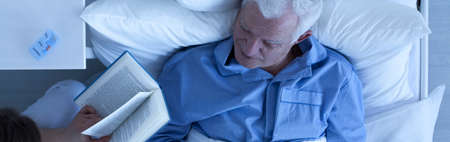 Photo from the top of carer reading the book to senior sick man in hospice Stock Photo