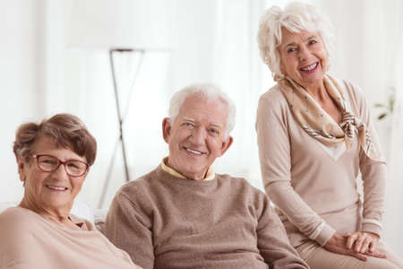 happy seniors: Happy group of seniors smiling, light background Stock Photo