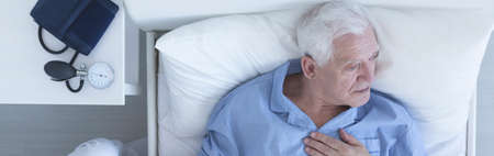 hurtful: Elderly man suffering from chest pain lying in hospital bed with pressure gauge on a nightstand Stock Photo