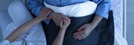 病院のベッドで眠っている看護師保持古い病気男の手の上からの写真 写真素材