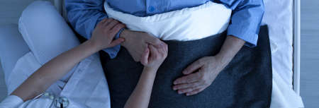 Photo from the top of nurse holding older sick mans hand who lies in hospital bed