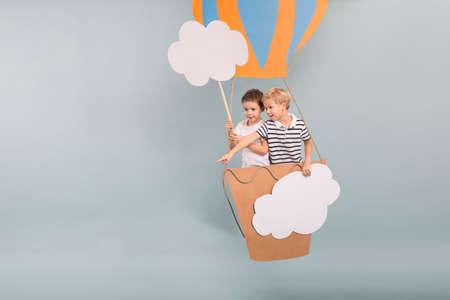 Creative siblings sitting in diy paper balloon