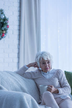 christmas spending: Sad senior woman sitting on a sofa and spending Christmas alone