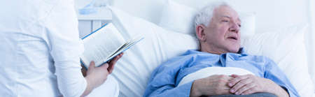 hurtful: Nurse in uniform reading a book to elderly sick patient lying in bed in hospice and suffering from pain