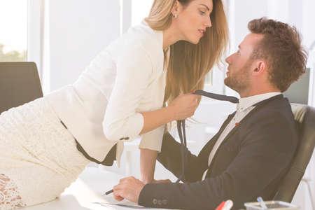 エレガントな男性のネクタイを押しオフィスで机の上に座っている美しい女性のショット