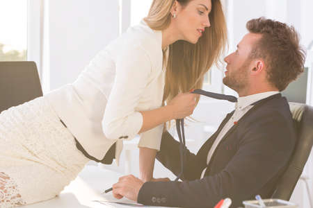 bossy: Shot of a beautiful woman sitting on a desk in an office and holding elegant mans tie Stock Photo