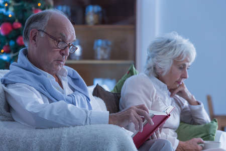 christmas spending: Sad elderly couple spending Christmas in a dark living room Stock Photo