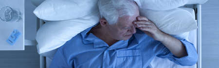 Elderly sick man with painful headache lying in bed in hospice with nightstand with medicine and glass of water