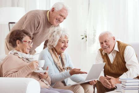 컴퓨터를 사용하는 노인들이 밝은 방에 앉아있다.