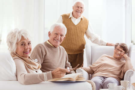 Happy pensioners of retirement home relaxing together