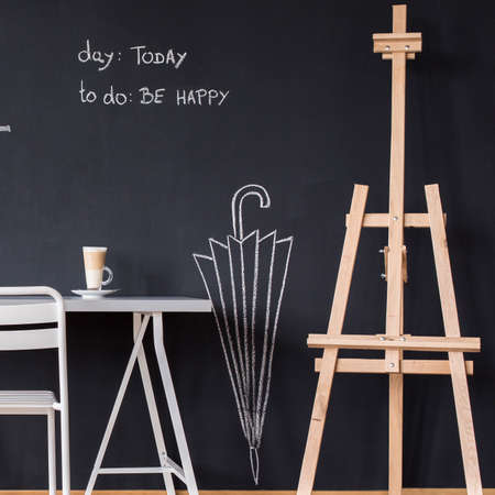 chalky: Minimalistic desk, chair and easel against blackboard wall with chalky drawings Stock Photo