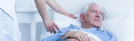 hurtful: Older sad lonely man lying in hospital bed with nurse helping him