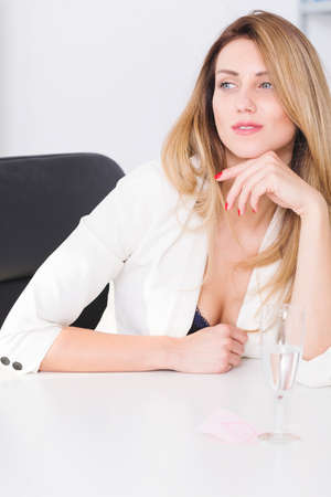 mobbing: Beautiful young businesswoman sitting in her office and looking seductively Stock Photo