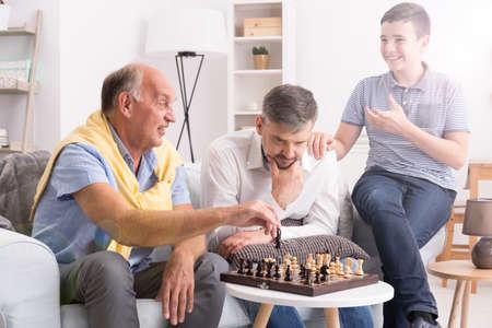 父と息子がチェスをして、少年はそれらを見て、笑みを浮かべて