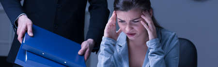 company person: Panoramic picture of a stressed young worker holding her head with her boss Stock Photo