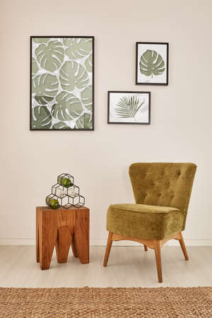 wall decor: White room with monstera leaf wall decor and green armchair Stock Photo