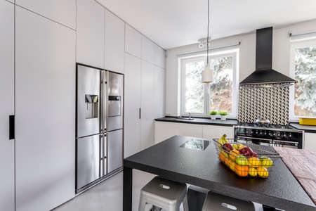 steely: Modern and light kitchen with steel fridge and stone table Stock Photo