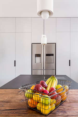 steely: Steel fridge in minimalist kitchen with fruit on the table