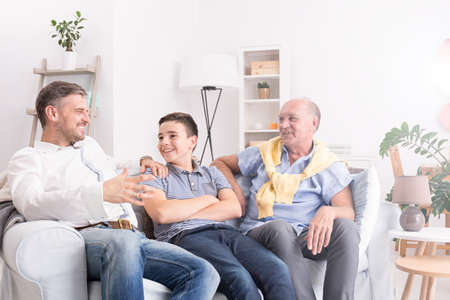 talk: Grandfather, son and grandson sitting on sofa and talking