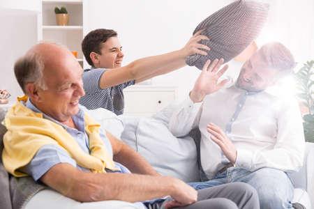 息子の父、ソファの上に座って幸せの祖父で遊んで