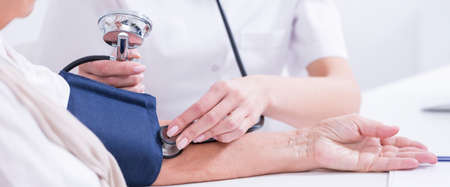 presure: Closeup shot of a doctors hand measuring elderly patients blood presure