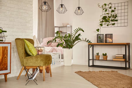 White home interior with green armchair and brick wall