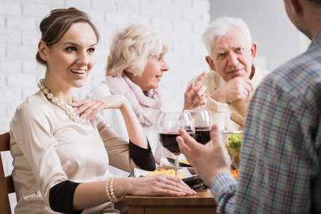 Shot of a modern family discussing together at dinner time