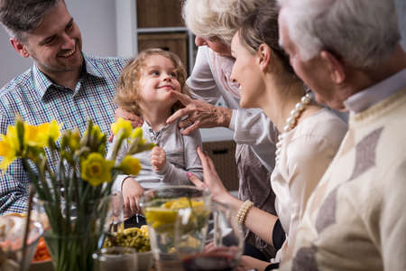 Three-generation family enjoying festive meal on the Easter day Imagens